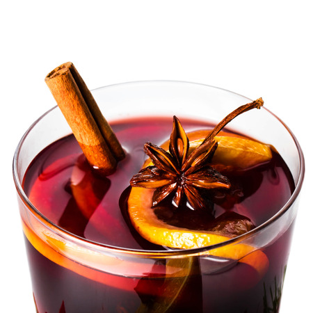 Hot red mulled wine for winter and Christmas with orange slice, anise and cinnamon sticks isolated on white background, closeup.