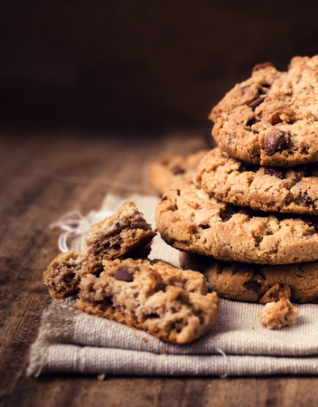 Chocolate chip cookies on natural linen napkin on wooden background with copy space.  Pile of chocolate chip cookies close up.