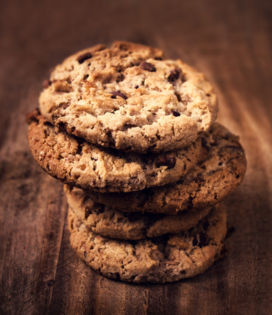 chocolate chip cookie: Chocolate chip cookies on wooden background. Stacked chocolate chip cookies shot with selective focus. Stock Photo