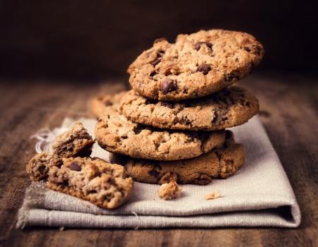 Chocolate Chip Cookies auf Leinentuch auf Holztisch. Gestapelte Schokoladenkekse hautnah. Standard-Bild