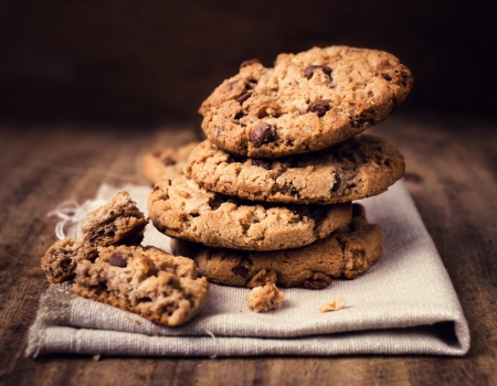 chocolates: Chocolate chip cookies on linen napkin on wooden table. Stacked chocolate chip cookies close up.