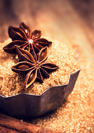 brown sugar: Brown sugar and Star Anise in a baking tray on wooden table, still life. Food background with copyspace. Festive background. Stock Photo