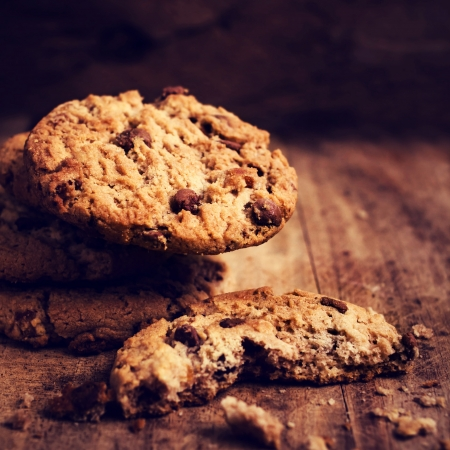 Chocolate cookies over wooden background in country style. Chocolate chip cookies pile shot on wooden table, macro