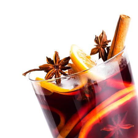 ホット クリスマスのスパイス、オレンジ スライス ・ アニス ・ シナモン スティックと白い背景で隔離赤いグリュー ワイン、クローズ アップ。