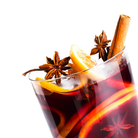 Hot red mulled wine isolated on white background with christmas spices, orange slice, anise and cinnamon sticks, close up.