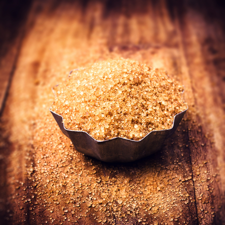 brown sugar: A pile of Brown Sugar in steel bowl, weathered wooden table background, selective focus.