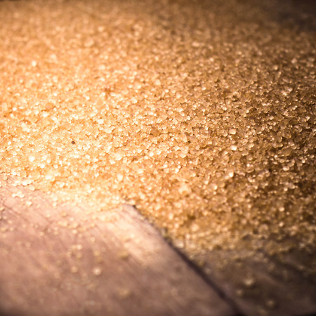 brown sugar: Food background with copy space. Shiny Brown sugar on wooden background close up, still life.