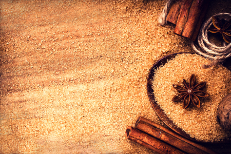 baking ingredients: Food background with copy space. Brown sugar, anise star and cinnamon sticks on wooden background close up, still life. Stock Photo
