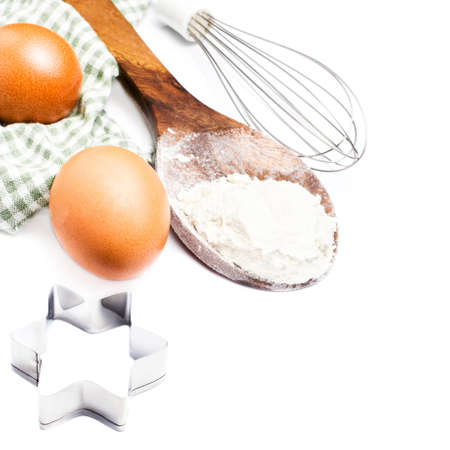 Festive cookie cutters,  eggs and flour for baking cookies isolated on white background.  photo
