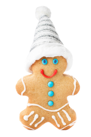 Christmas Gingerbread Man Cookie with Santa hat isolated on white background, closeup. photo