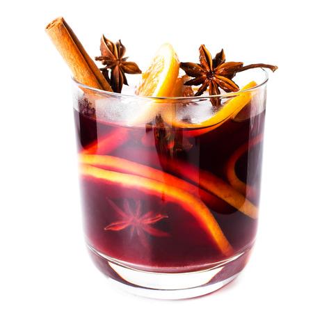 ホット クリスマス スパイス、オレンジ スライス、アニス、シナモン棒と白い背景で隔離赤いホットワイン、クローズ アップ。