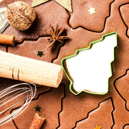 festive food: Christmas background with Gingerbread baking dough, cookie cutters, spices and nuts. Christmas festive food, top view, closeup. Stock Photo