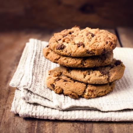 カントリー スタイルの白いナプキンにチョコレート チップ クッキーを積み上げ。チョコレート チップ クッキーは、セレクティブ フォーカスと木