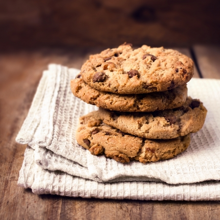 Stacked chocolate chip cookies on white napkin in country style. Chocolate chip cookies shot on wooden table with selective focus. Foto de archivo