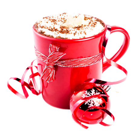 Red Christmas coffee cup topped with whipped cream and with christmas decorations on white background