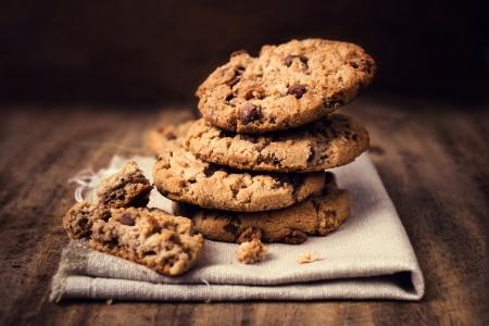 나무 테이블에 흰색 리넨 냅킨에 초콜릿 쿠키. 초콜릿 칩 쿠키, 커피 색깔의 천에 근접 촬영.