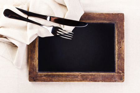 Vintage blackboard with wooden frame with linen towel and serving cutlery.  Blank chalk board with copy space.  photo