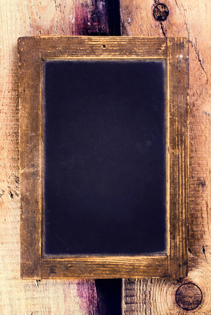 Vintage blackboard with wooden frame hanging on old wooden background. Blank black  chalk board with copy space.  photo