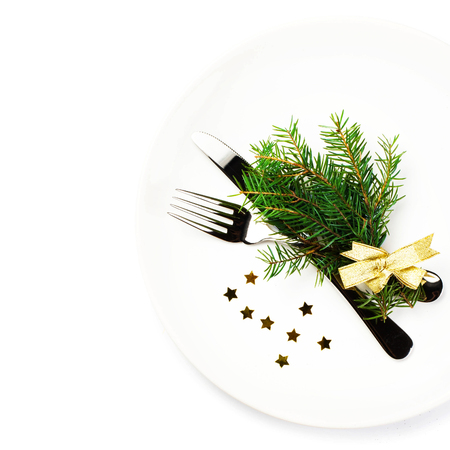 Christmas table setting with festive decorations on white plate isolated on white . Christmas tree branch, golden stars, Fork and knife with copy space, top shot. photo