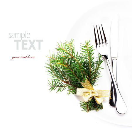 Festive  table setting with Christmas ornaments and copy space for text. Christmas tree branch,  Fork and knife on white plate isolated on white .  photo