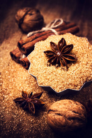 Food background with copyspace. Brown sugar and Star Anise in a baking tray on wooden table, still life. Festive background. photo