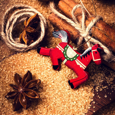 festive food: Christmas background with Cinnamon sticks,  Brown sugar, anise star  and red horse on wooden table close up, still life. Festive Food background.
