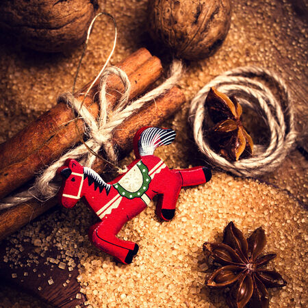 festive food: Christmas background with Spices. Cinnamon sticks, Brown sugar, anise star and red horse on wooden table close up, still life. Festive Food background. Stock Photo