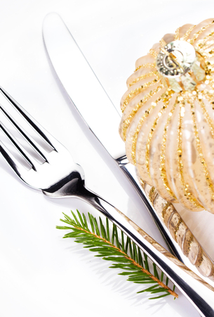 Festive  table setting with Christmas ornaments and copy space for text. Christmas fir tree branch and golden ball  on white plate isolated on white background, close up. photo