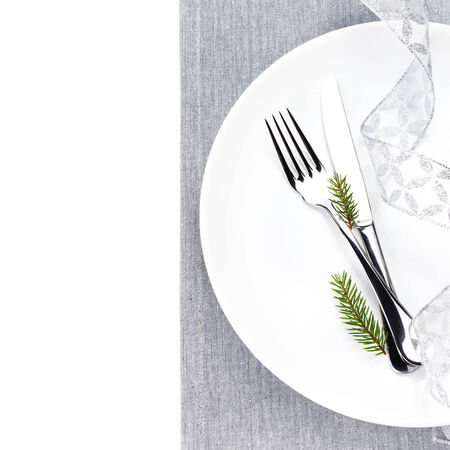 Bright Christmas table setting place with festive decorations on white plate isolated. Christmas fir tree branch, silver ribbon,  Fork and knife  with copy space, top shot. photo