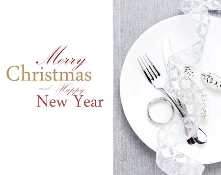 Elegant Christmas table setting with christmas  decorations on white plate and gray napkin isolated on white background.  Fork and knife with copy space for text. photo
