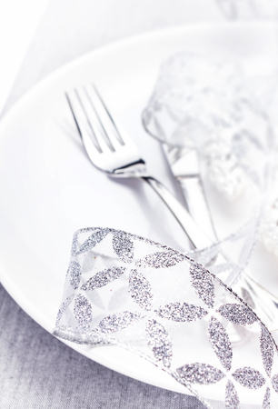 Elegant Christmas table setting with festive decorations on white plate with silver ribbon close up.   photo