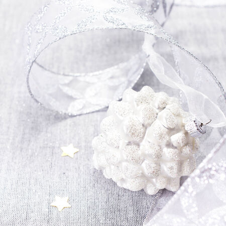White Christmas. Christmas Decorations with white pine cone, golden stars  and silver ribbon close up. Christmas card with copyspace for greeting text. photo