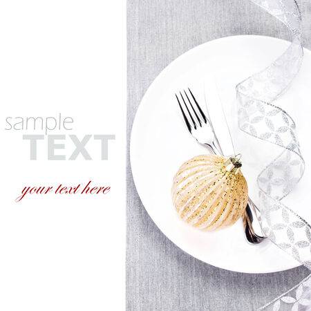 Elegant Christmas table setting with festive ornaments on white plate isolated. Shiny golden Christmas bauble, Fork and knife with silver ribbon  with copy space. photo