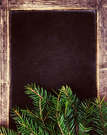 Christmas tree branches on Vintage Christmas Blackboard frame. Retro slate chalk board  photo