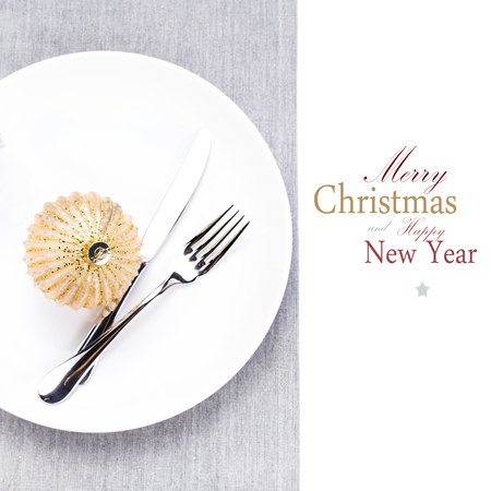 Christmas table setting place with festive ornaments on white plate isolated. Shiny golden Christmas ball, Fork and knife  with copy space for greeting text, close up. photo