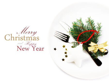 Christmas table setting with festive decorations on white plate isolated on white background. Christmas tree branch, golden stars, Fork and knife with copy space for text. photo