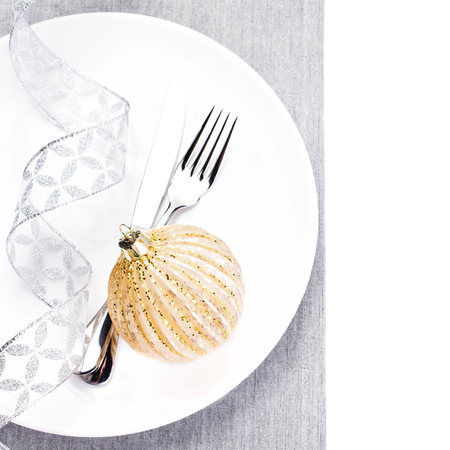 Elegant Christmas table setting with festive decorations on white plate isolated. Shiny golden Christmas ball, Fork and knife with copy space for text. photo