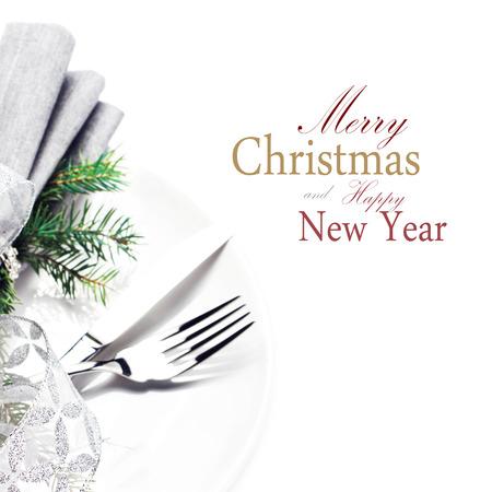 クリスマスの飾りと白いプレートの白い背景で隔離のあいさつ文をコピー スペースを持つテーブルの場所設定をモミの木の枝とクリスマスをクロー 写真素材