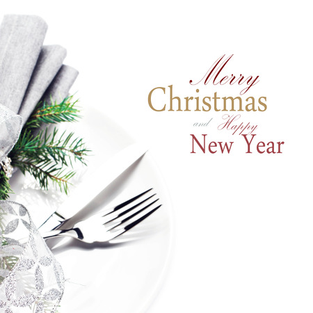 Fir Tree Branch and Christmas table place setting with christmas ornaments and copy space for greeting text on white plate  isolated on white background, close up.