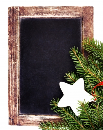 Vintage slate chalk board with Christmas ornaments isolated on white background. Christmas Tree Fir branch on old Blackboard frame.