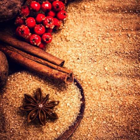 festive food: Cinnamon sticks,  Brown sugar and anise star with red berries on wooden table close up, still life. Festive Food background.