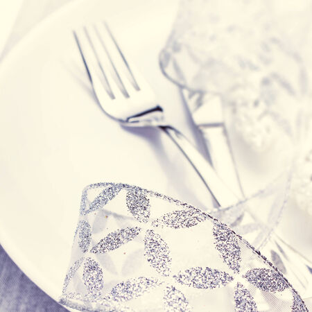 Christmas table setting with festive decorations on white plate with silver ribbon macro photo