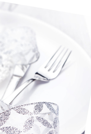Elegant table setting place with festive decorations on white plate with silver ribbon isolated on white background,  close up.   photo