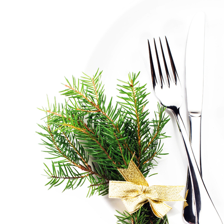 Christmas table setting with festive decorations on white plate isolated on white background. Christmas tree branch, golden stars, Fork and knife with copy space, macro. photo