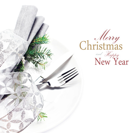 Elegant Christmas table setting place with festive ornaments on white plate isolated. Shiny golden Christmas ball, Fork and knife with copy space for greeting text, close up. photo
