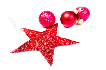Christmas Decorations isolated on white backhrouns. Festive Red Star and red balls close up with copy space for greeting text. photo