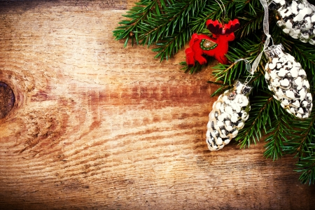 Christmas Tree Branch on wooden background with wood deer and silver pine cones with copy space for greeting text. Christmas ornaments close up.  photo