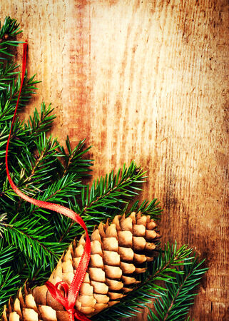 Christmas Card with Tree Branch on wooden background with festive ribbon and pine cone with copy space for greeting text. Christmas ornaments close up.  photo