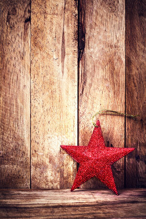 Vintage Christmas ornaments on wooden background. Rustic Christmas Decoration. Old fashion Red Star on wood with copy space for greeting text.