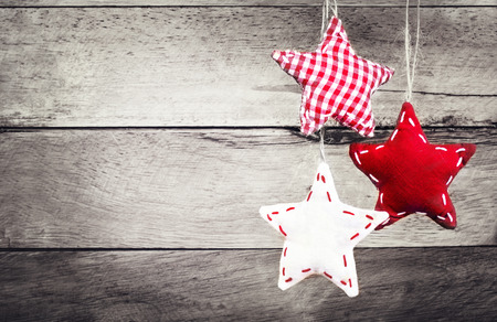 weihnachtsschleife: Weihnachtsschmuck h�ngen �ber rustikale Holz Hintergrund. Weinlese-Weihnachtskarte. Old Fashion Rote Sterne auf Holz Board mit Kopie Platz f�r Gru�text.